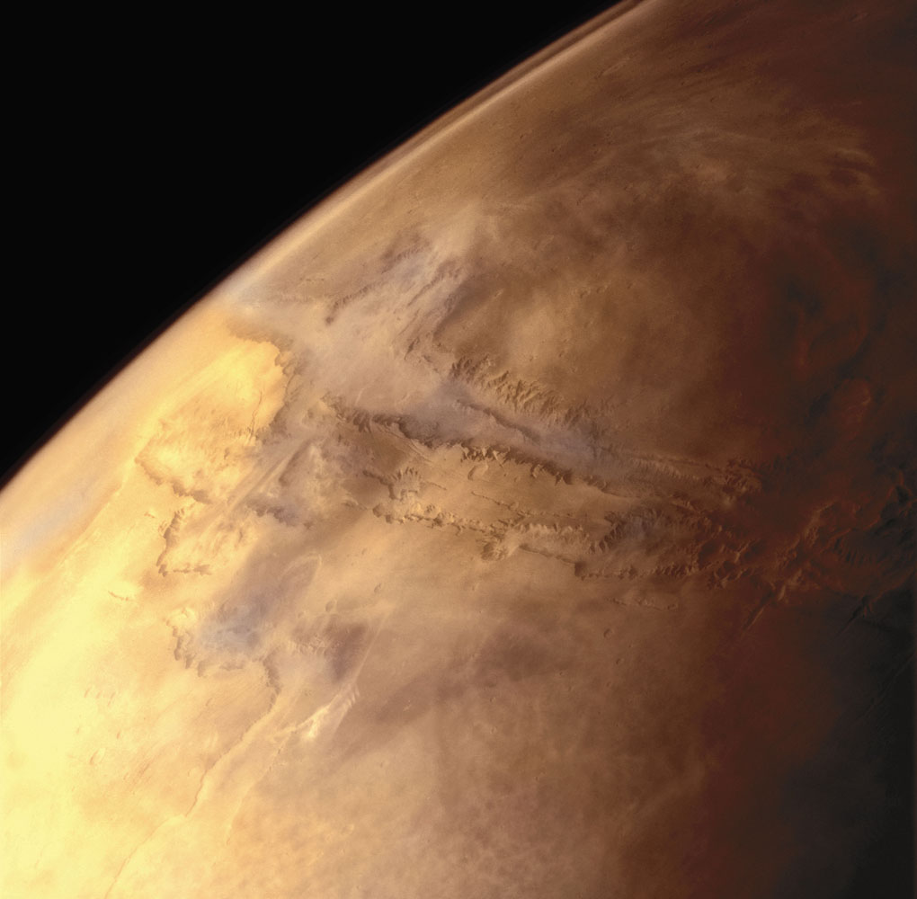 The largest canyon in the Solar System, Valles Marineris is almost 2,500 miles long—nearly as long as the continental United States is wide. A ground fog hugs the canyon floor. Haze in the thin Martian atmosphere is visible on the horizon.                               Multi-frame mosaic Viking Orbiter 1, July 16, 1978
