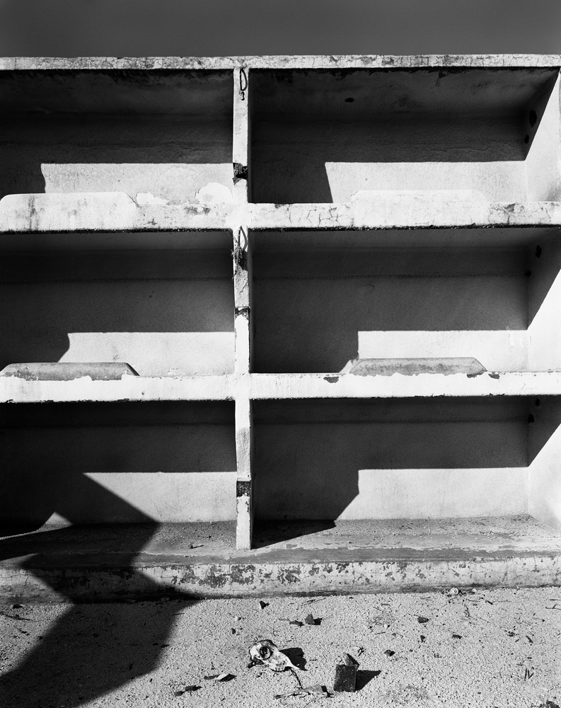 """Mineworkers' bunks in the abandoned Chinese compound of the Simmer and Jack Mine, Germiston. July 1965.                               To meet an acute shortage of labour, mine-owners brought some 63 000 indentured Chinese labourers to the gold mines between 1904 and 1910. To ensure tight control of their movements, closed compounds, similar to those used on the Kimberley diamond mines, were built to house them. Outer walls had no windows. Entry and exit were via a guarded gate. The men were repatriated to China in 1910. However, the advantages of closed compounds in the housing and control of labour had been clearly demonstrated and, until the late 20th century, the design was henceforth applied to compounds housing Black migrant workers. Rooms sleeping 20 to 40 men in concrete bunks were common. Late in the 20th century terminology changed and compounds came to be called """"hostels"""". They also came to be more comfortable and were """"open"""" in design."""