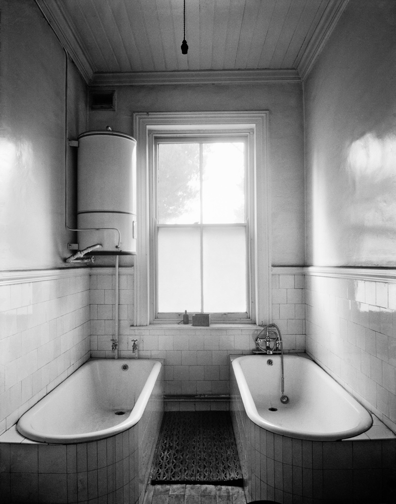 """Attached to the General Manager's office was his bathroom with a """"dirty"""" bath and a """"clean"""" bath for his use after being underground, New Kleinfontein, Benoni. May 1967."""