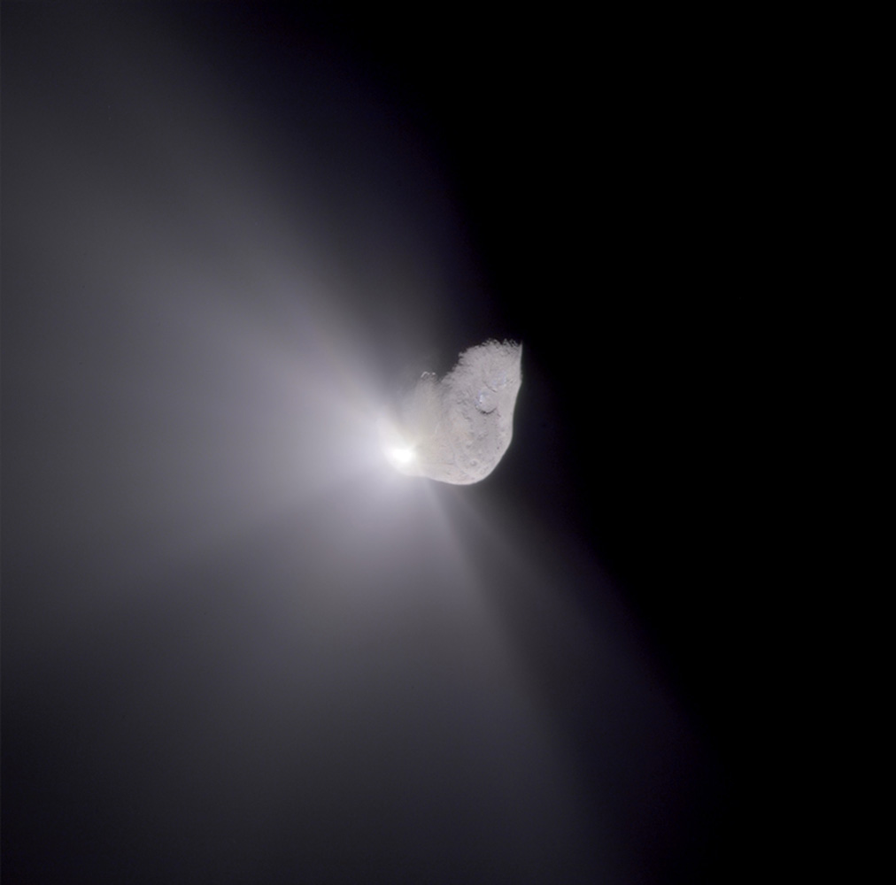 Nucleus of periodic comet Tempel 1 soon after being struck by a projectile launched from the Deep Impact spacecraft. A cloud of dust and ice expands in space.                               Deep Impact, July 4, 2005