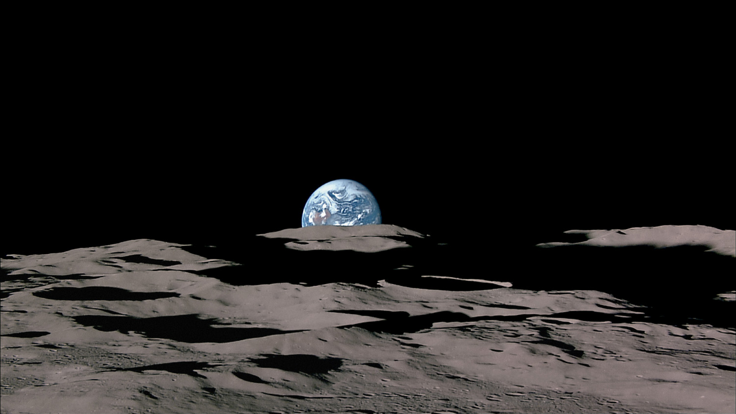 Earthrise at the Moon's south polar horizon, with Shackleton Crater in the foreground. We're upside down,  with Australia visible at the top of the terrestrial globe. Because Earth always hangs in the same position above the Moon's near side, it never seems to rise or set from a fixed location—but in this case, the spacecraft's motion makes it appear to.                               Kaguya, Nov. 7, 2007