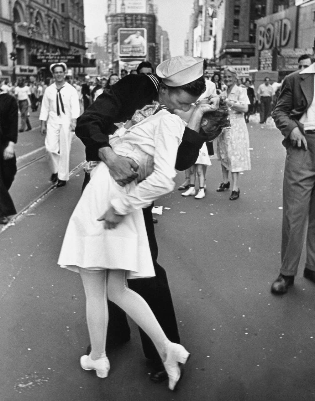 A jubilant American sailor clutching a pretty white-uniformed nurse in a joyful, back-bending, passionate kiss while thousands jam the Times Square area to celebrate the long awaited victory over Japan.