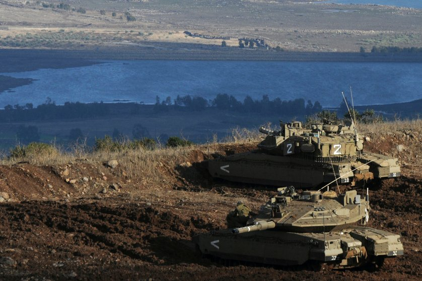 Image: Nov. 12, 2012. Israeli tanks stand in position overlooking a Syrian village from the Israeli-occupied Golan Heights.