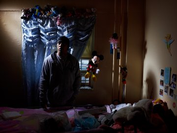 "Image: David Stephens stands beside the hospital bed in his daughter Tatiana's room. The owner of a hair salon–named Three Angels Hair Salon after his daughters–until the economy forced him to shutter the business, David cares for his daughter in his sixth floor apartment in the Redfern Houses. Tatiana, now 17, suffered a brain infection at 9 that left her paralyzed. The morning after Sandy, David carried her down six flights of stairs after the power went out. Tatiana is staying with Stephens' mother-in-law. ""This is the time to show who's down for what,"" Stephens says of the Redfern community. ""Everybody can walk past on a nice day and say, 'I'm your neighbor.' But when there's tough time, where are you at? No we're all standing on line. Now we're all looking for help."""