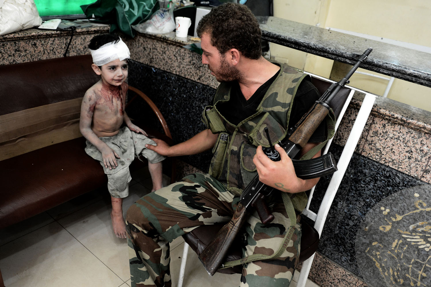 Aris Messinis                                An FSA fighter tries to calm down a wounded child after his house, which was about 100 meters from the hospital, was hit by a helicopter's rocket. The boy was carried to the hospital by neighbors and, after the first treatment, was moved to the reception area. With dozens of civilian casualties that afternoon by air strikes, many of them children in worse conditions, the hospital was running out of space. The boy was standing there alone, so the fighter stayed with the boy until other members of his family arrived at the hospital to pick him up.                                                              Covering the impact of war on nonfighting civilians — receiving the consequences of it without even participating — is of a much greater importance than the proper war-news coverage. When there are people experiencing these situations, the least you can do is inform the world about these changes on their lives and present realities — changes that could be unimaginable to others.
