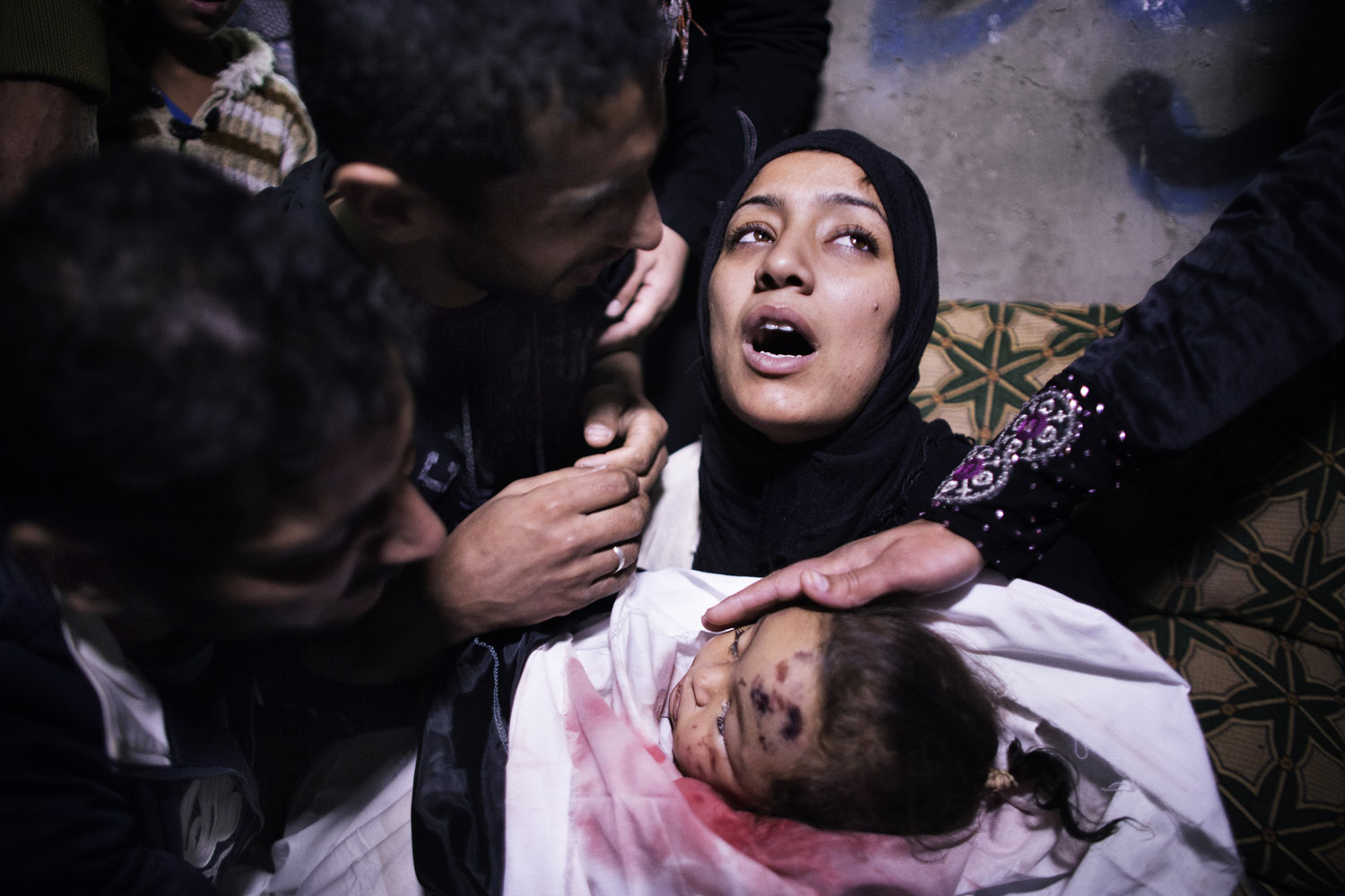 Nov. 16, 2012. The mother of a 10-month-old Palestinian girl killed the day before in an Israeli air strike is comforted by her husband and relatives as she mourns before her daughter's funeral in Gaza City.