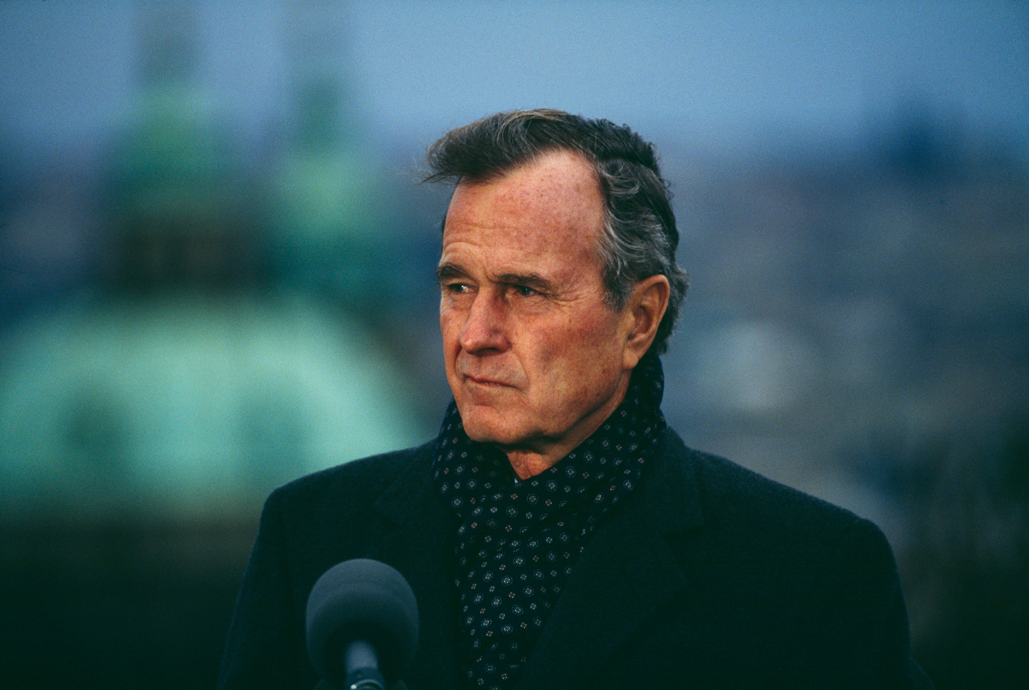 President George H.W. Bush bundled-up against autumn chill, speaking while visiting Prague, Czechoslovakia, November 18, 1990.
