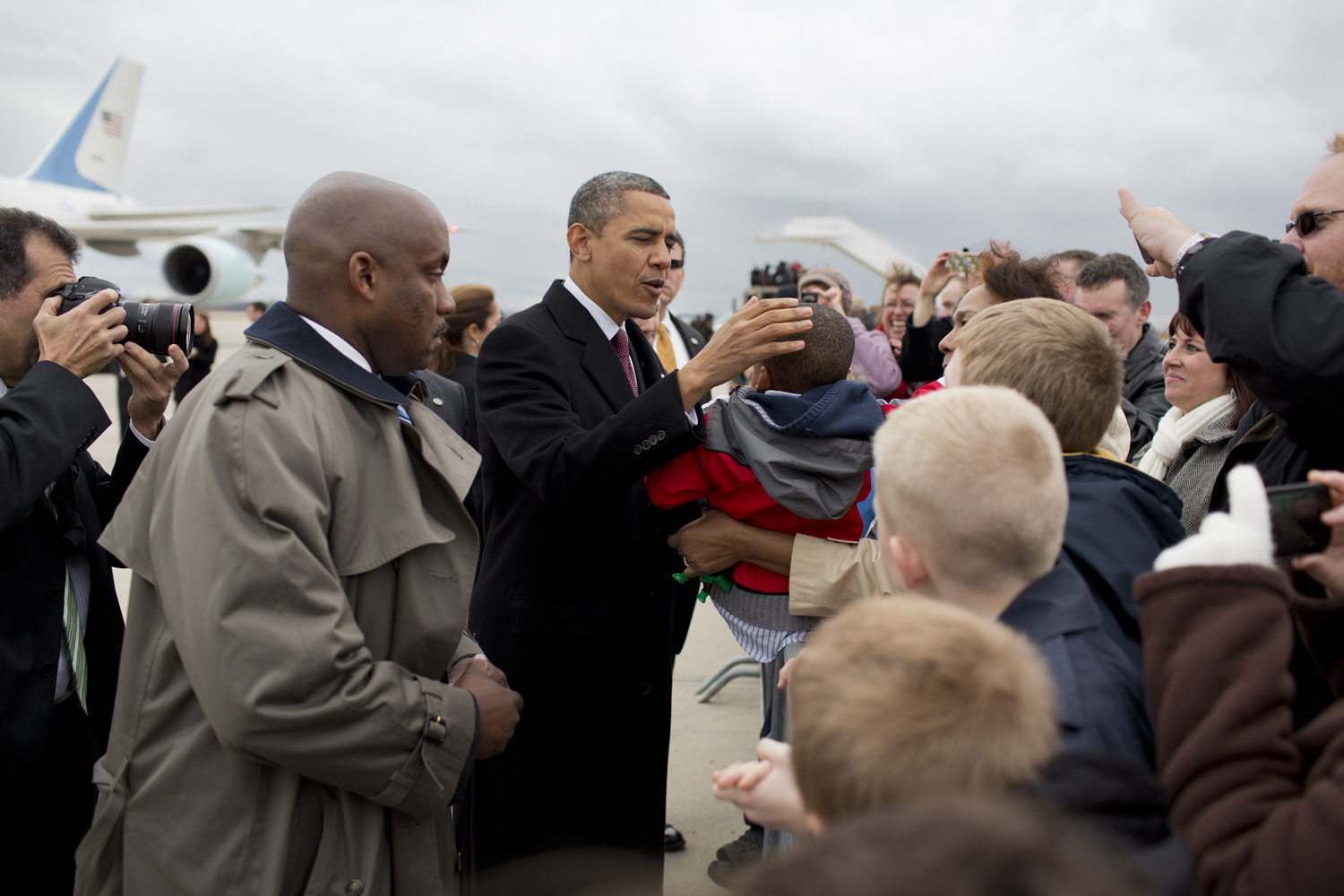Arriving at the airport in Redford, Mich., Obama greets local officials and a small crowd on the tarmac.