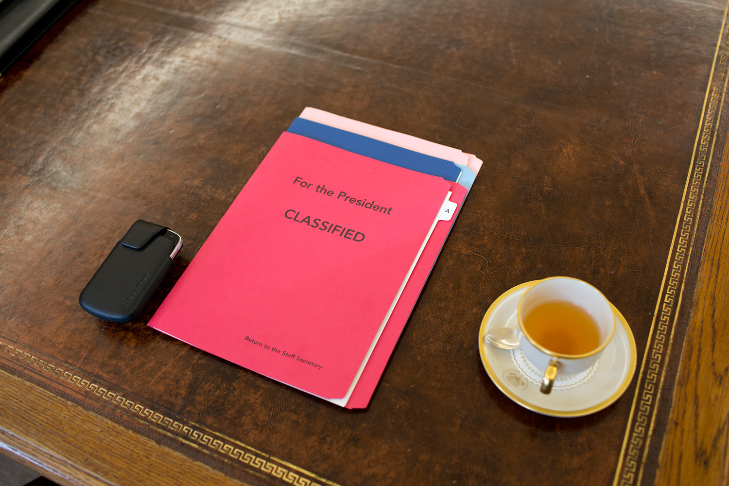 The President's BlackBerry, briefing and cup of tea on his Oval Office desk.