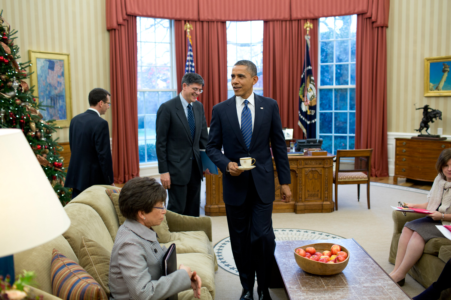 The President carries his tea before a senior staff briefing in the Oval Office.