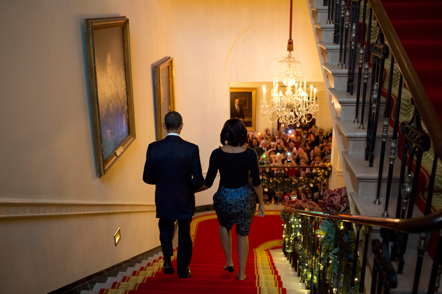 President Obama and First Lady Michelle Obama descend the White House staircase to a packed audience attending a Christmas party.