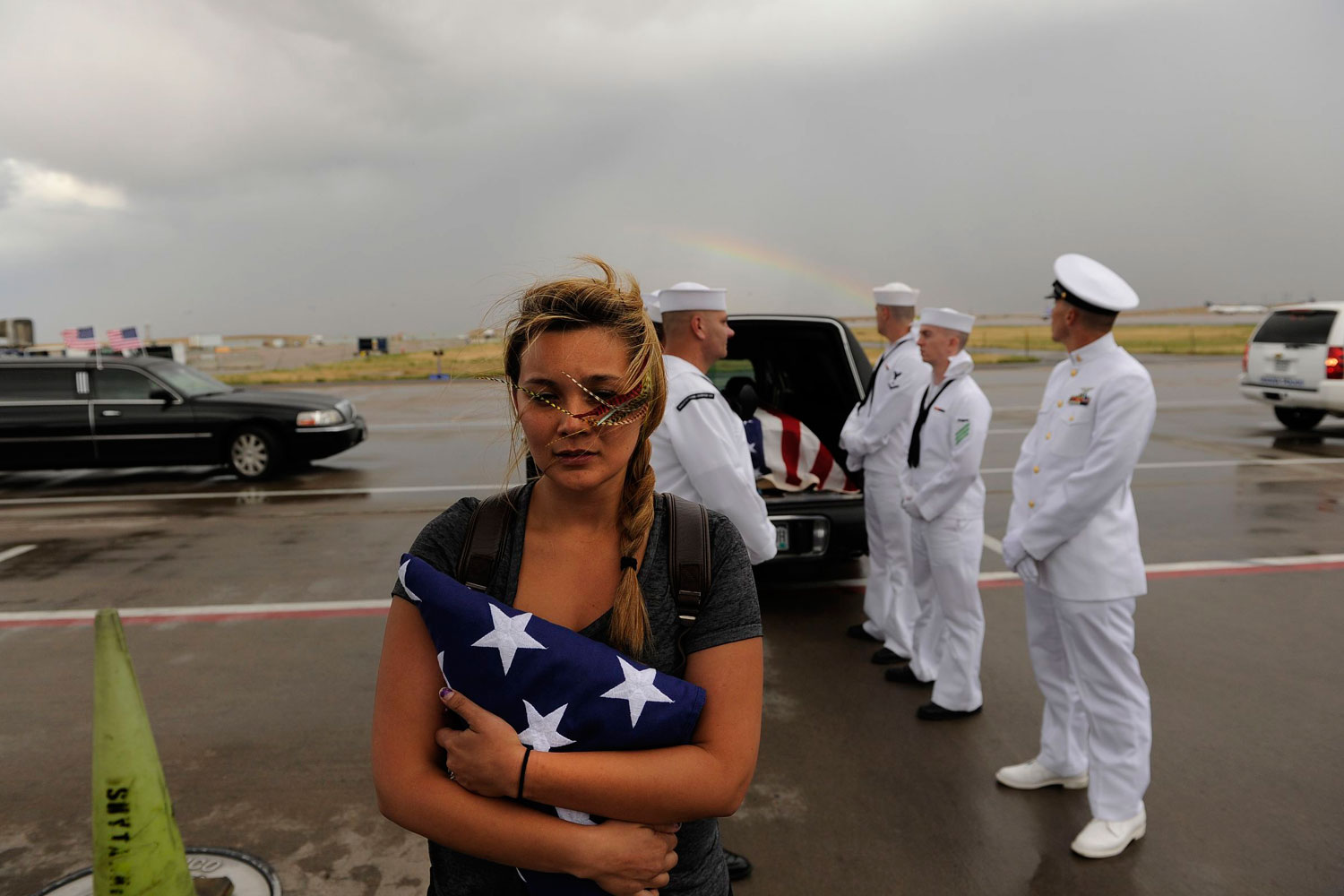 No More Shooting Massacres                     July 27, 2012. A rainbow appears behind Chantel Blunk, wife of Jonathan Blunk, as the flag-draped casket bearing her husband's remains is loaded onto a plane at Denver International Airport. Blunk, a five-year U.S. Navy veteran, was killed in the July 20 Dark Knight Rises shooting massacre in Aurora, Colorado.