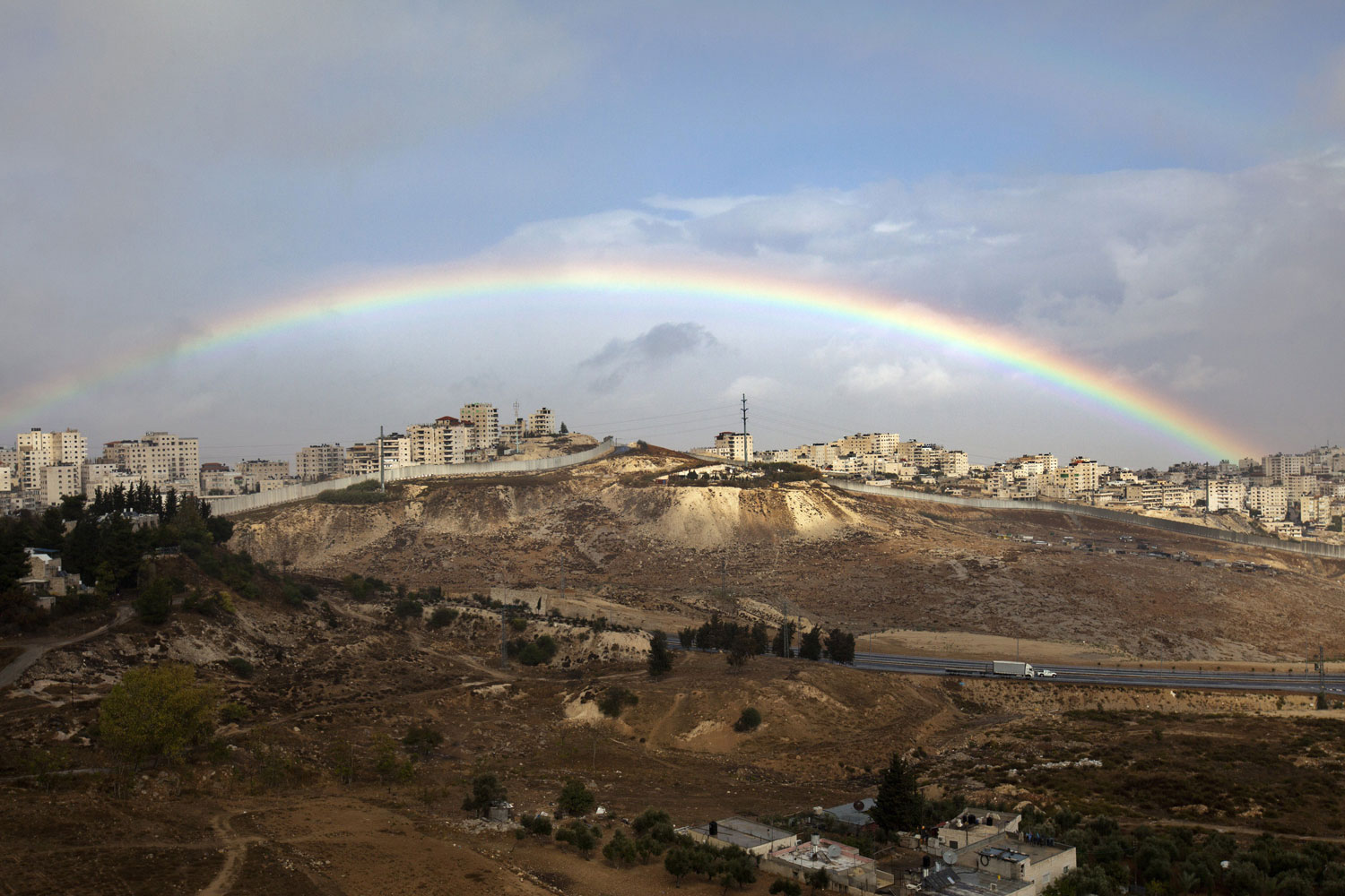 Coexistence, not Sectarianism                               Nov. 11, 2012. A rainbow arcs over the Palestinian Shuafat refugee camp and a section of Israel's controversial separation barrier in Isreali-annexed East Jerusalem.