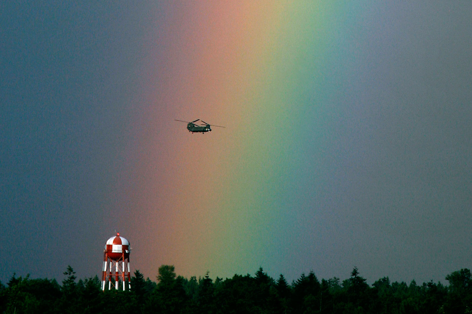 The Safe Return of Those Who Serve                               June 25, 2012. A Chinook helicopter passes before a rainbow as it maneuvers north of DuPont, Wash.
