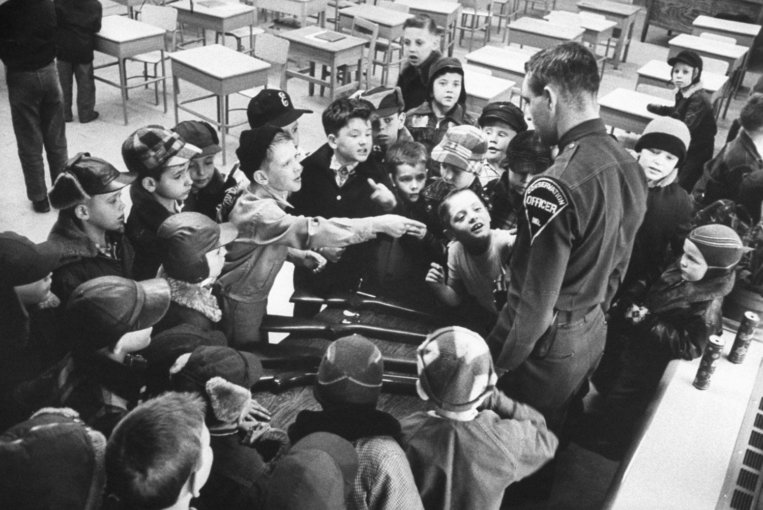 <b>Caption from LIFE.</b> In safety class instructor Rod Rankin is bombarded by Hobart, Ind., boys with questions about gun display and cartridge case in his belt.