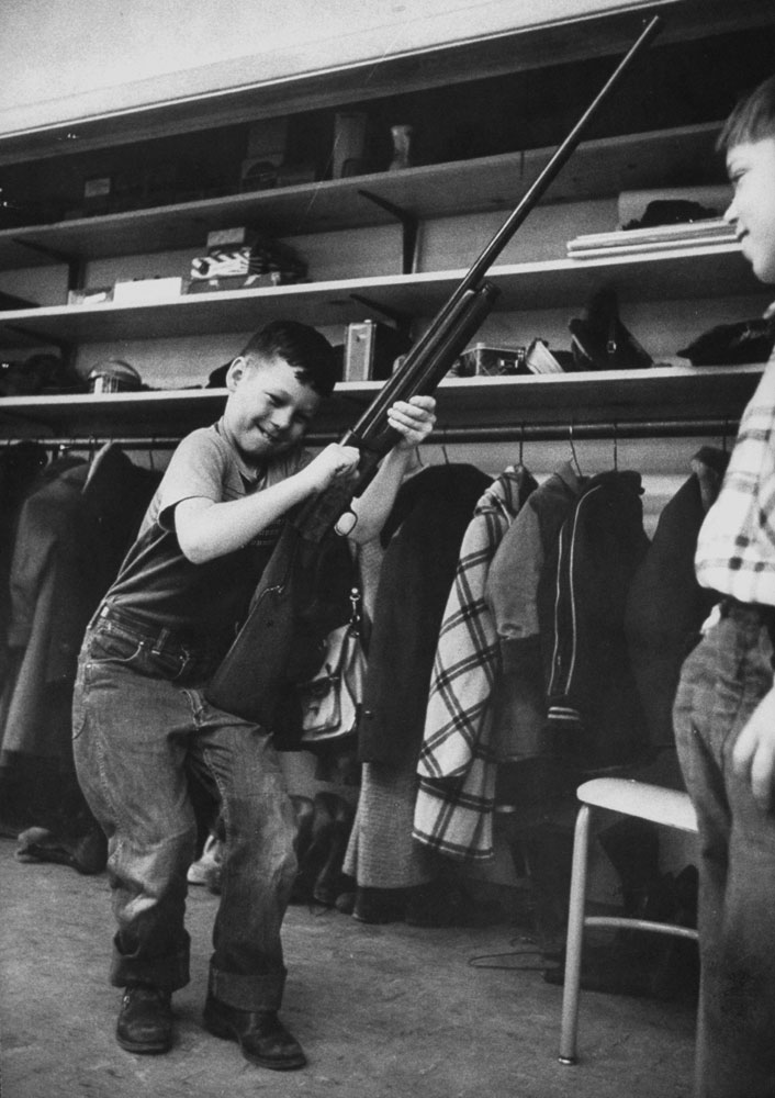 <b>Caption from LIFE.</b> Drawing bolt on 12-gauge shotgun, Johnny Cherela, 7, grimaces as he follows Rankin's instructions to check the chamber to see if gun is loaded.