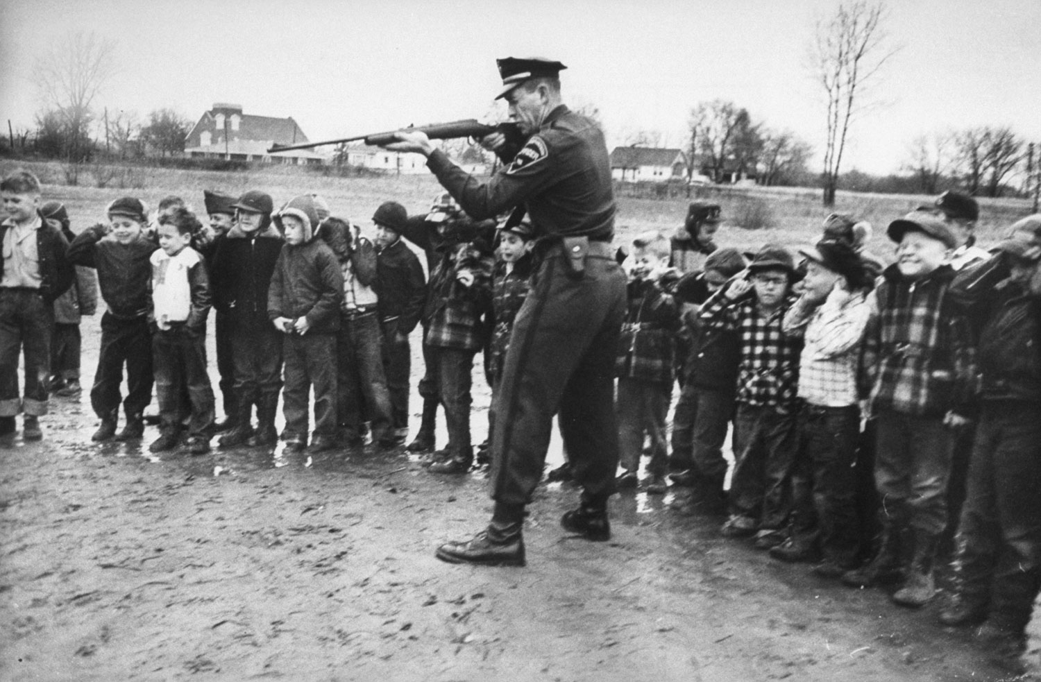 <b>Caption from LIFE.</b> Cringing class holds breath and ears as Rankin aims 30-30 rifle at can of water in demonstration to impress kids with the destructive power of guns.