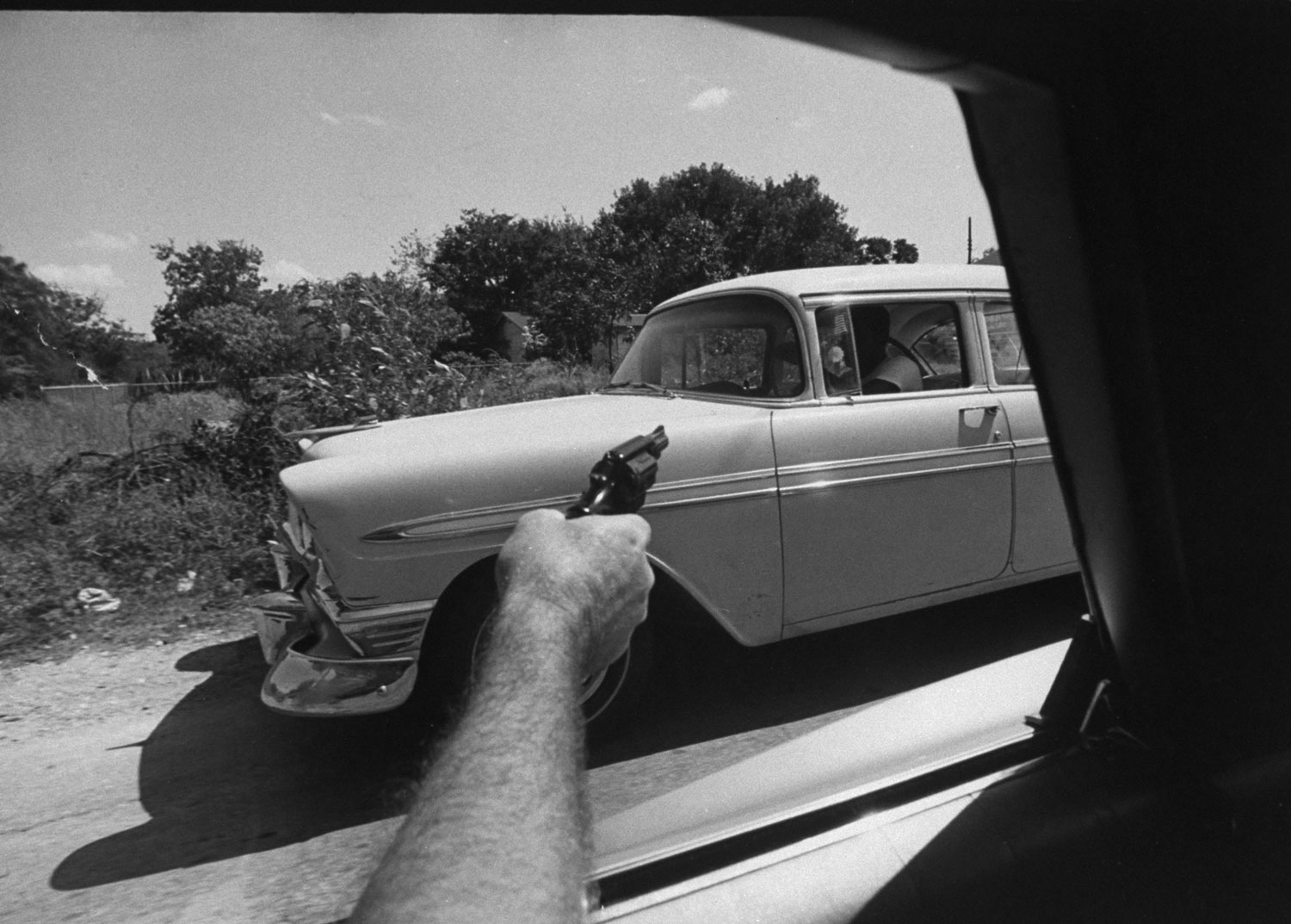 A U.S. Customs agent points his gun at a car suspected of transporting marijuana, 1969.