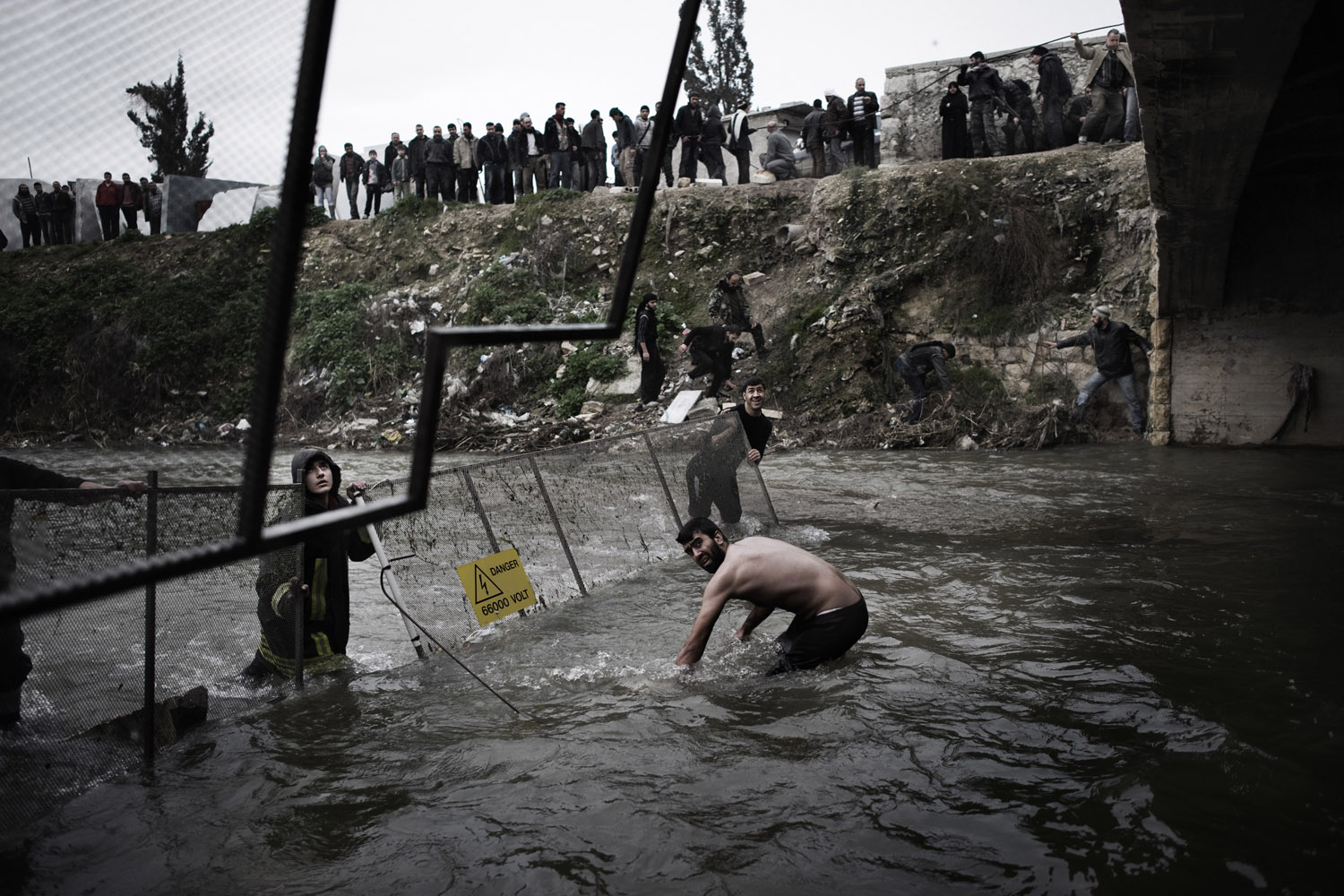 The day after victims of the massacre were first discovered, officials moved fencing into the river to help catch additional bodies as they floated downstream near Aleppo, Jan. 30, 2013.