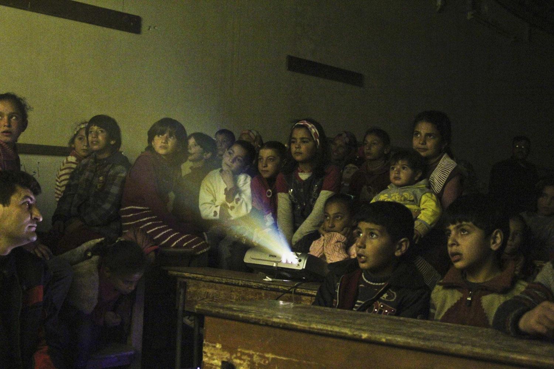 Jan. 16, 2013. Internally displaced children watch cartoons in a classroom of a school in Kafranbel in Idlib province, Syria.