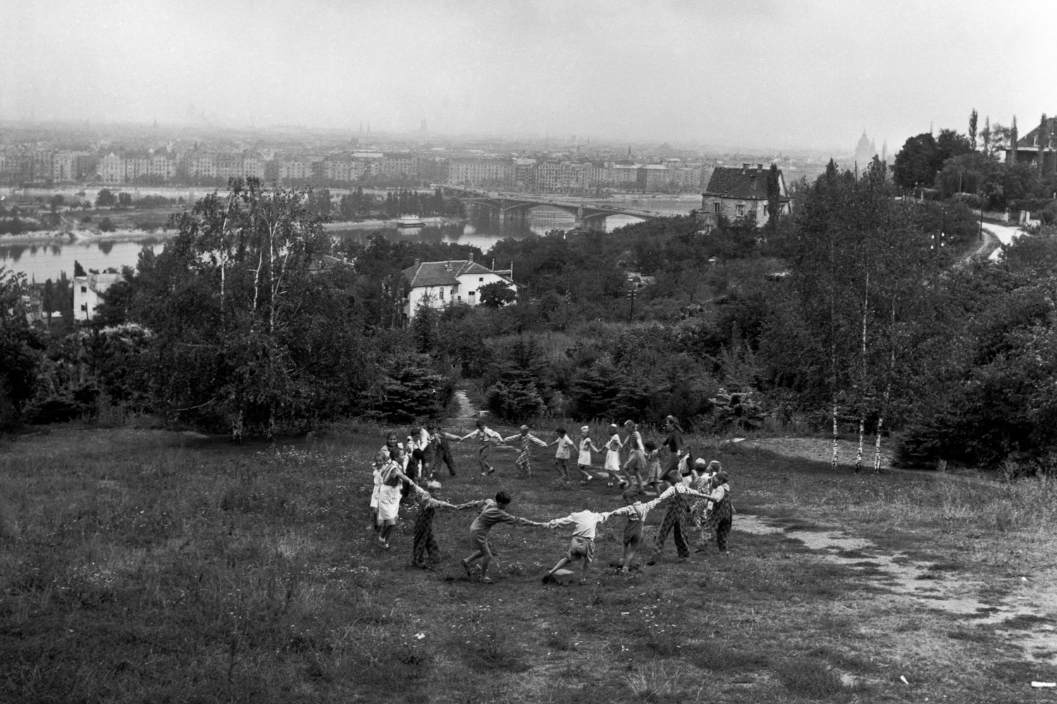 Children playing in a suburban park. Behind lies the Danube with the newly built Margareten Bridge. The theme of Ring a Ring o' Roses, often contrasting with a ruined landscape, is recurrent in Chim's work as well in his colleague Werner Bischof's post-World War II European work. Budapest, Hungary. 1948.