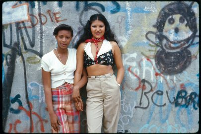 Two Latin girls pose in front of a wall of graffiti in Lynch Park, in Brooklyn, New York, 1974.