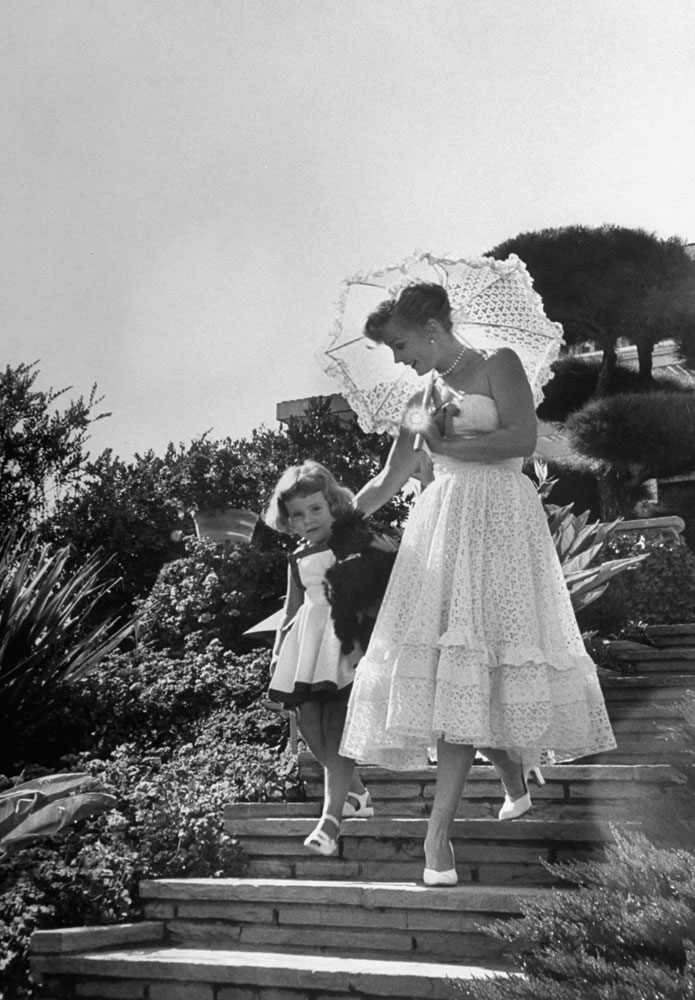 <b>Caption from LIFE.</b> A 25-carat glow is shed by her ring as Zsa Zsa Gabor takes daughter [Francesca, by hotel magnate Conrad Hilton] walking at their Bel Air home.