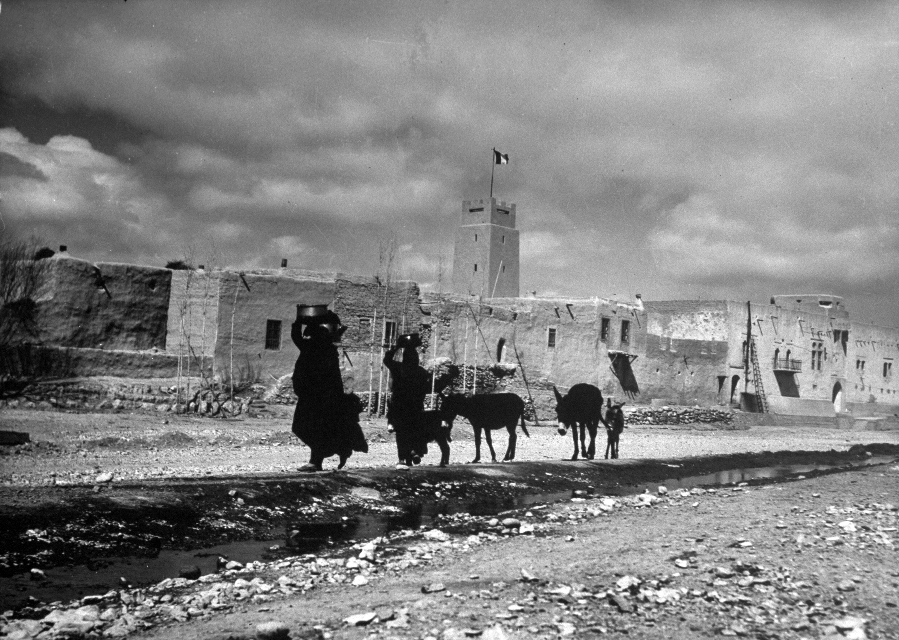 Women carry water containers on their heads as they lead mules along a road in a desert village near Damascus, Syria, 1940.