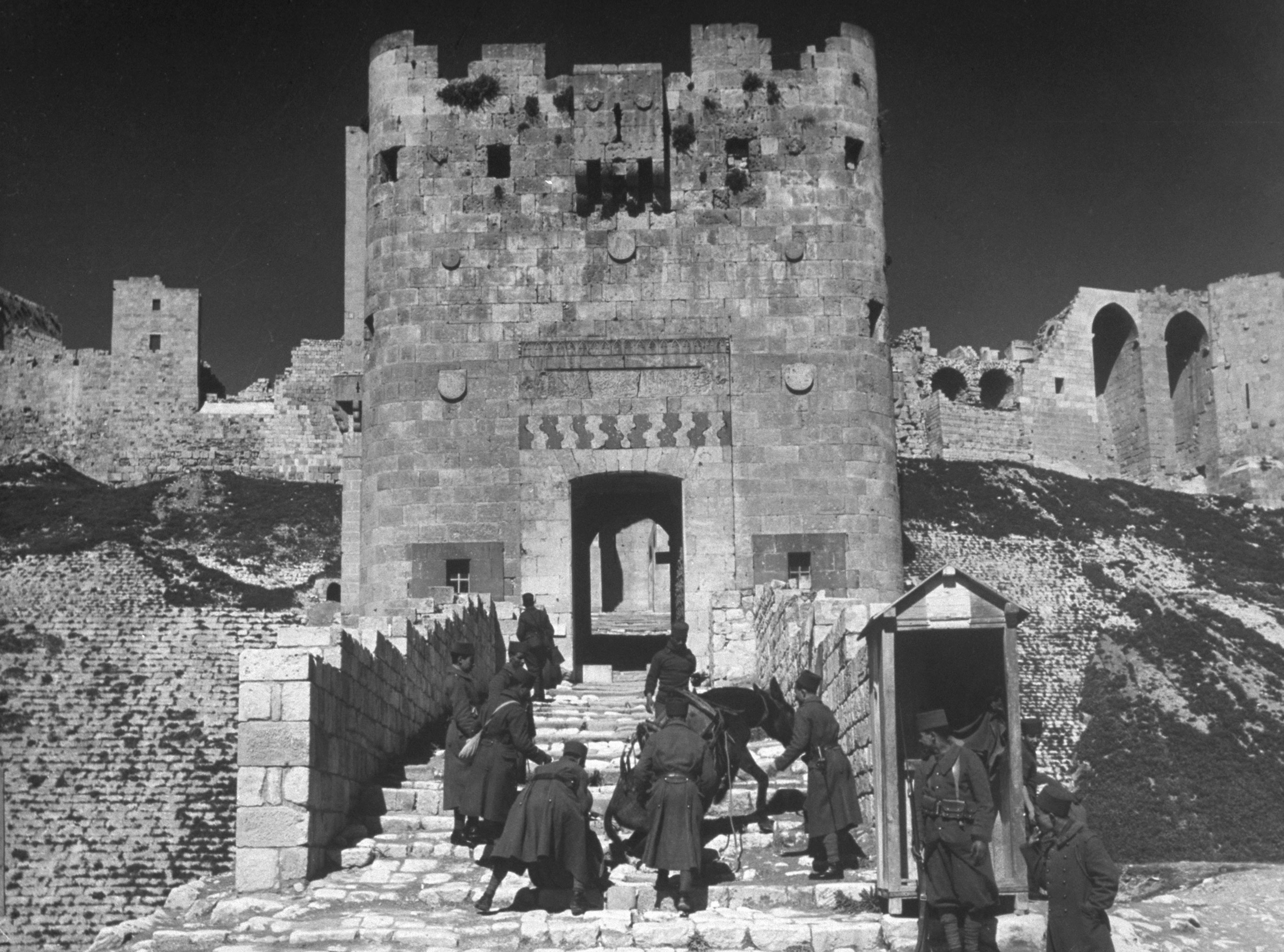 Soldiers urge a mule up the steps of the citadel at Aleppo, Syria, 1940.