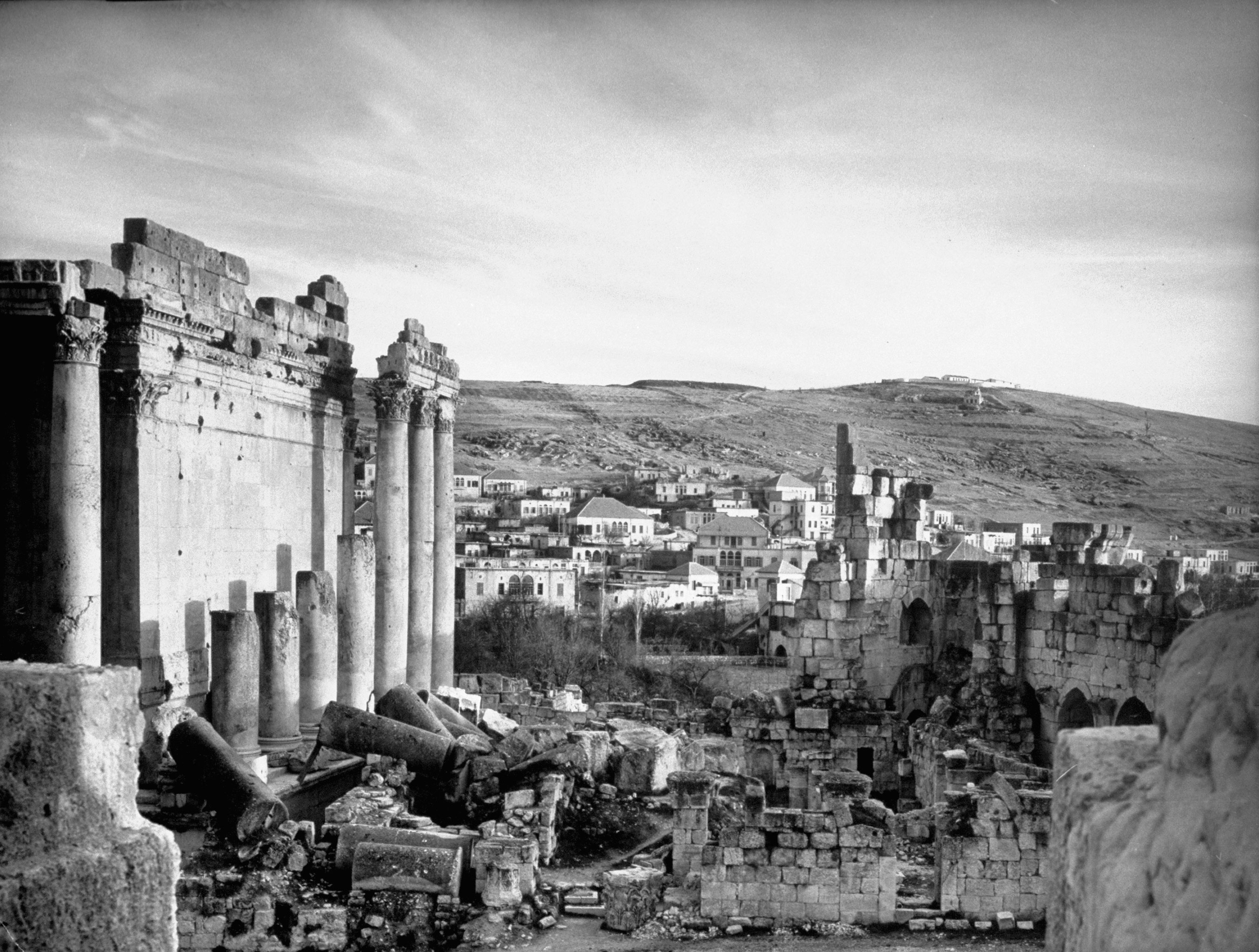 Archaeological ruins with modern homes in background, Syria, 1940.
