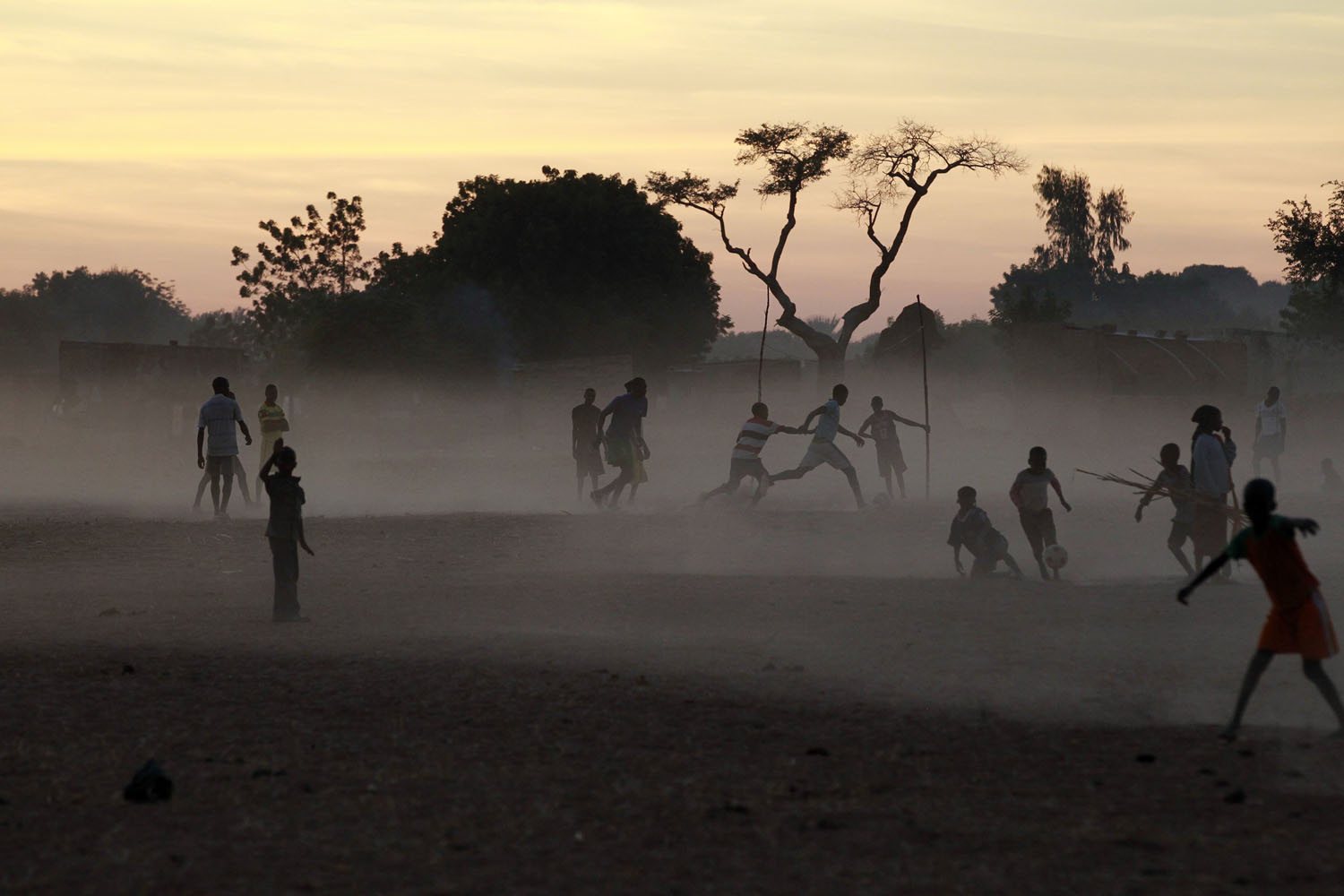 Children and adults alike play soccer on a dusty field in Segou, central Mali, Jan. 21, 2013.