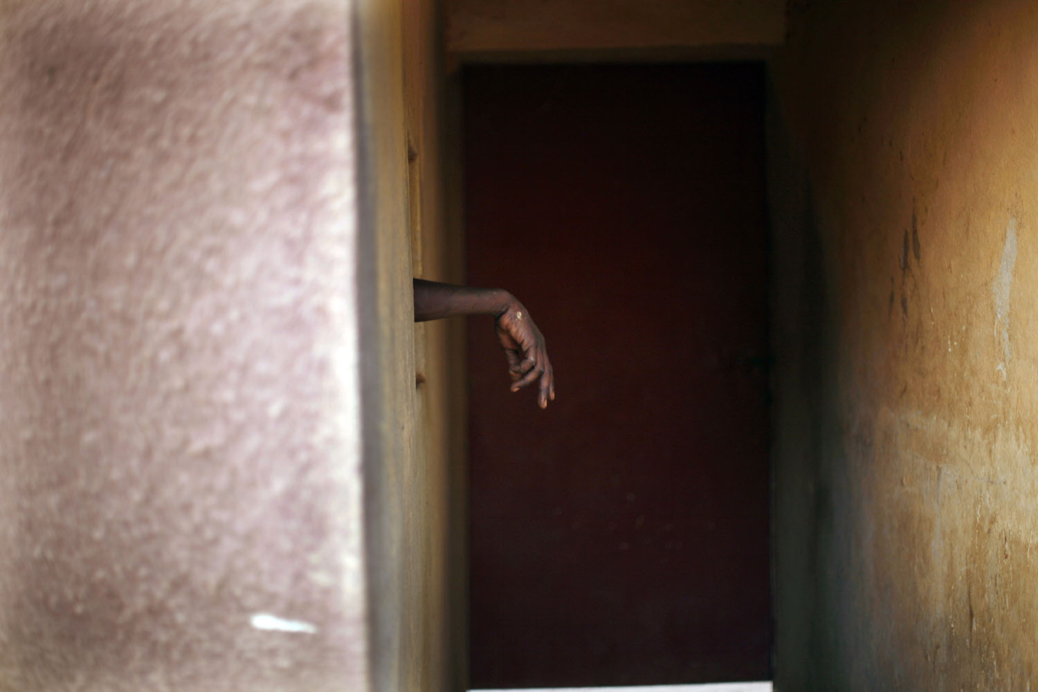 A suspected member of MUJAO sticks his hand out of the cell where suspected  fighters are held in Gao, Feb. 11 2013.