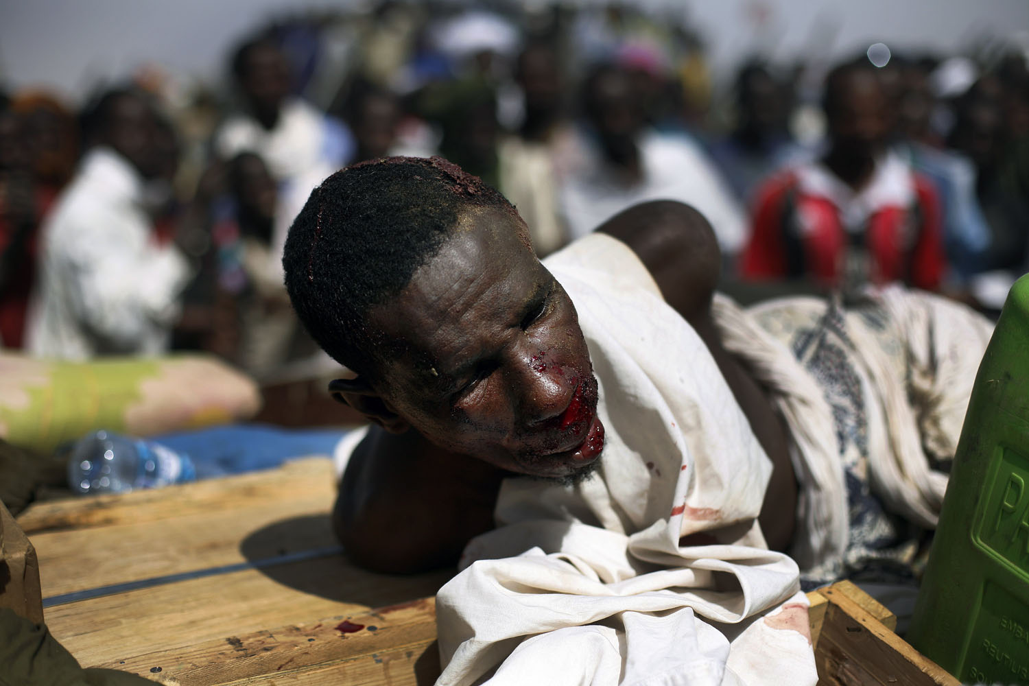 A suspected Islamist extremist who was beaten by the crowd lies in the back of an army truck in Gao, Jan. 29, 2013. Four suspects were arrested after being found by a youth militia calling themselves the  Gao Patrolmen.  Malian soldiers prevented the mob from lynching them.