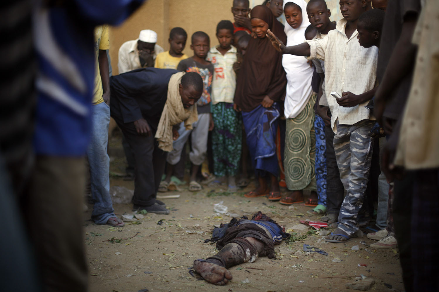 Malian people gather around the leg of an Islamic fighter outside the police station in Gao, Feb. 11, 2013.