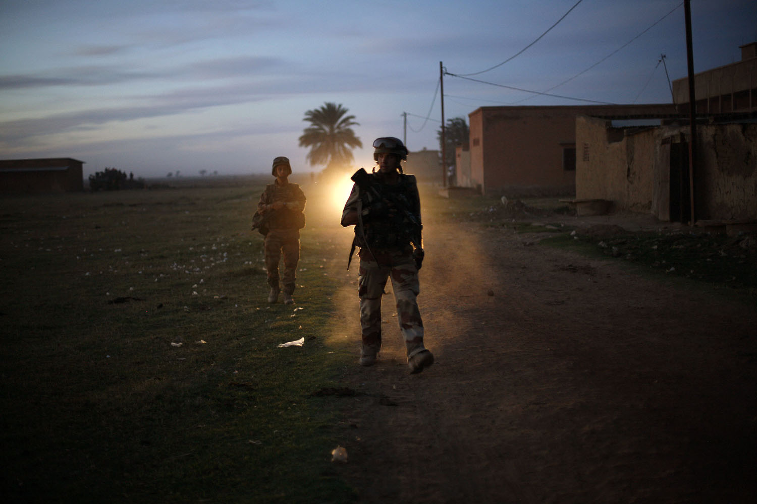 A French soldier waits for a French Puma transport helicopter to land on the soccer stadium to test the field in the center of Niono, some 400 kms (300 miles) North of the capital on Jan. 20, 2013.