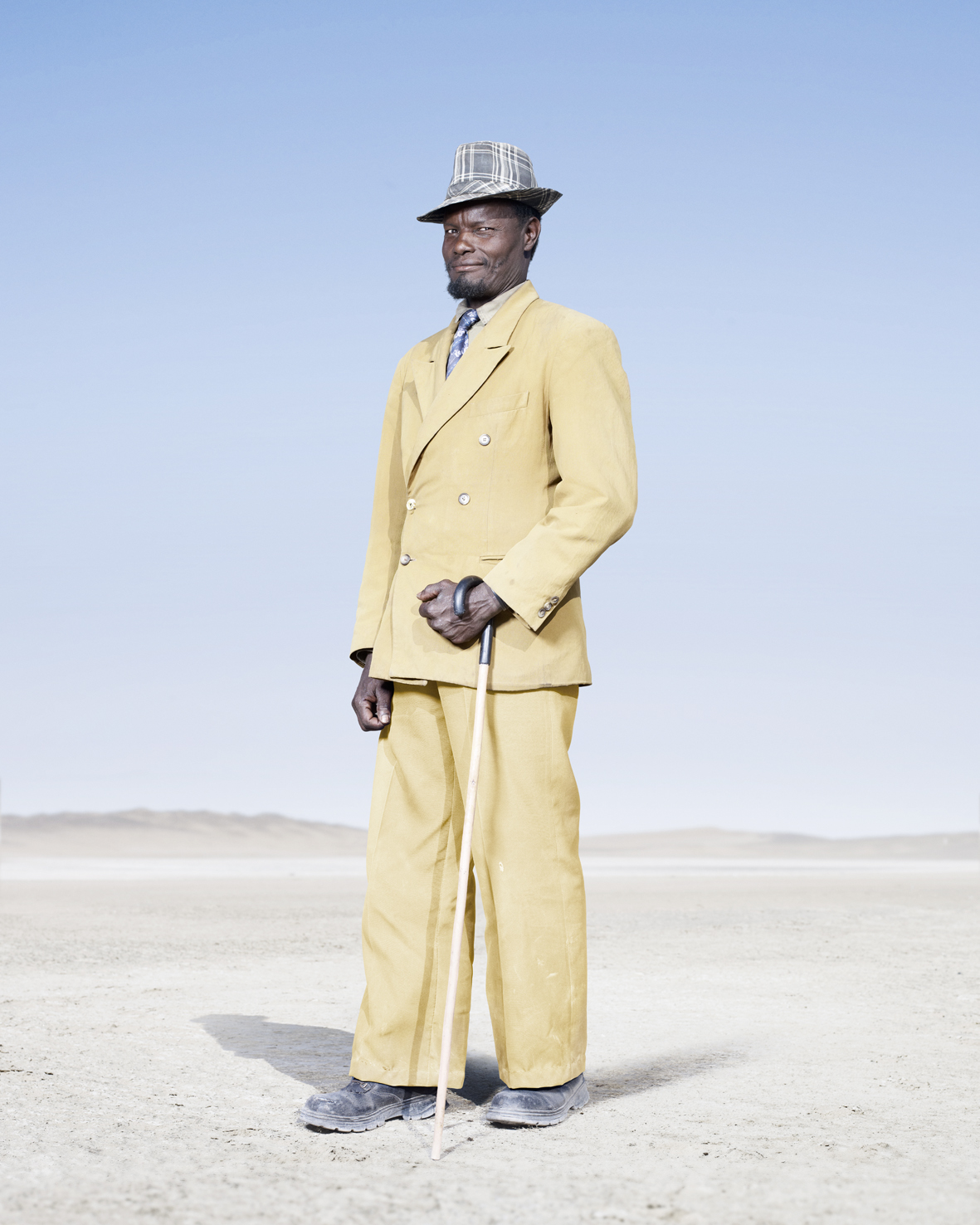 The tradition of wearing formal attire is maintained by most Herero elders, such as this man in a yellow double-breasted suit and check trilby. It is, however, noticeably in decline among younger Herero man, who tend to favor jeans and a t-shirt.