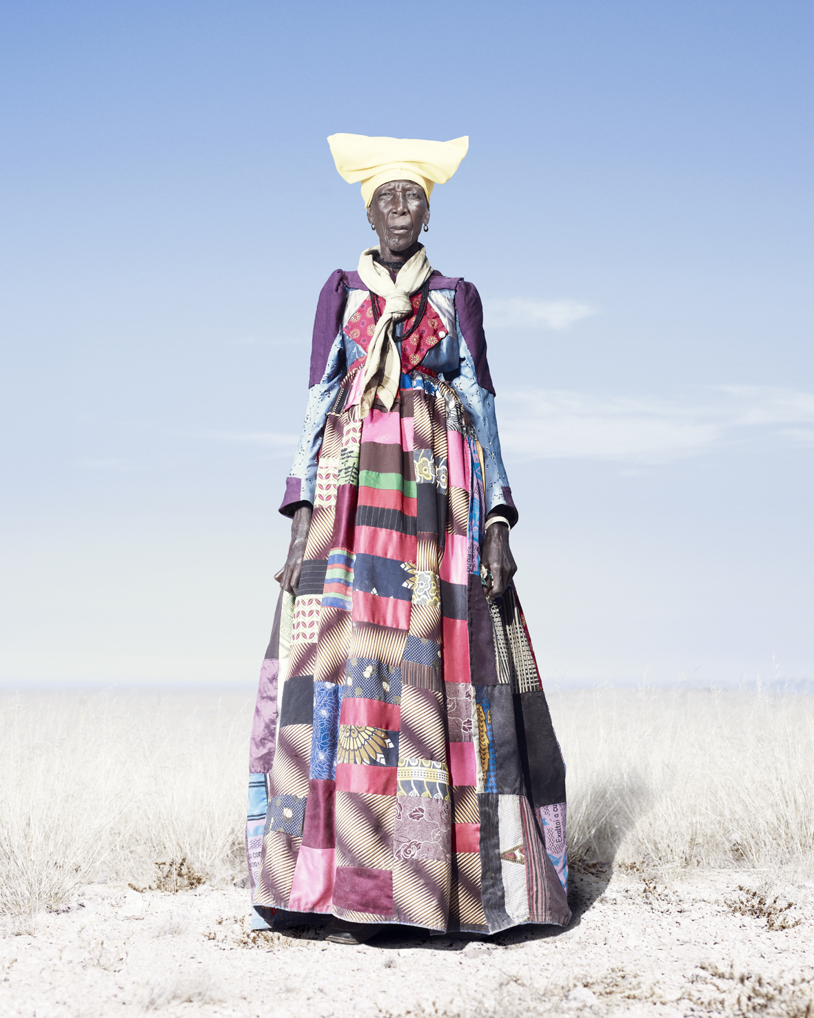 An elderly Herero woman in patchwork dress and pale scarf. As Herero women get older, the 'horns' of their headdresses get smaller. According to some accounts, this is to symbolize their loss of fertility.
