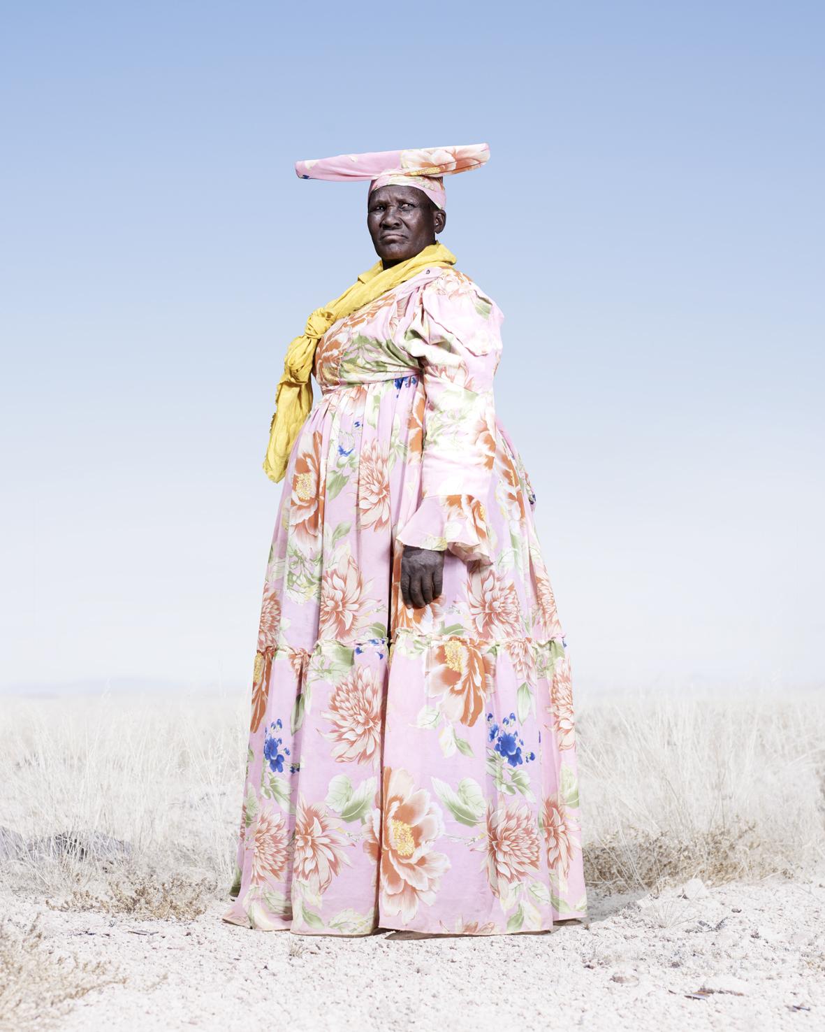 Herero women wears a yellow scarf and traditional headdress.