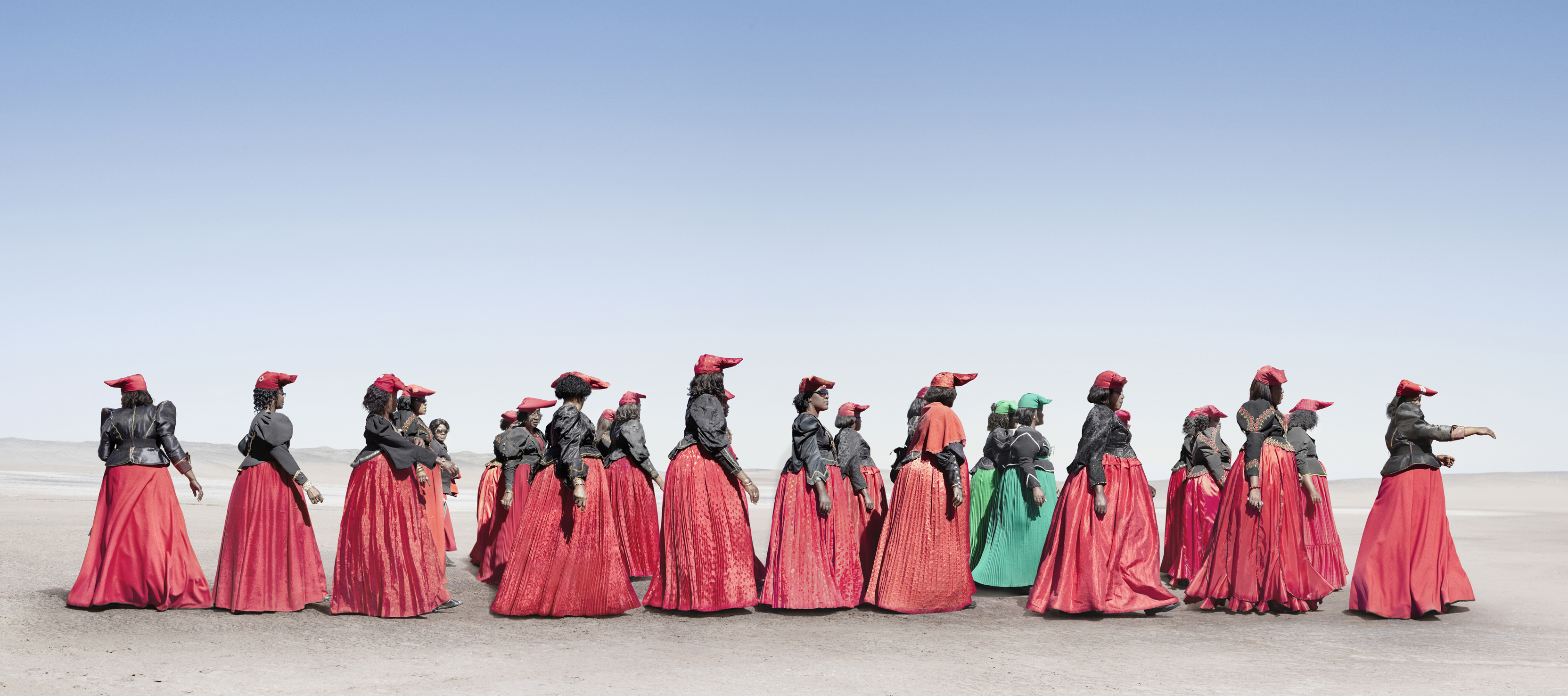 Conspicuous by their presence, two women from the Otjigrine section of the Otruppe march alongside a group of women from the Otjiserandu. The women's formal, or 'military' dresses are worn on ceremonies and festivals like Herero day, which is held every August to commemorate Herero chiefs of the past.