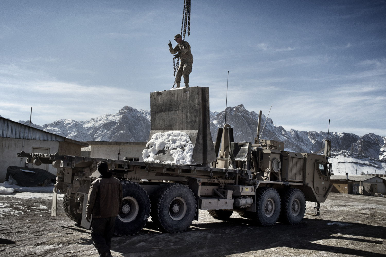 A soldier from Bull Battery, 4-319th Airborne Field Artillery Battalion loads concrete blocks on a truck in preparation for leaving Forward Operating Altimur, Logar Province, Afghanistan.