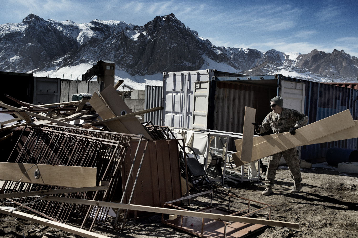 A soldier from Bull Battery, 4-319th Airborne Field Artillery Battalion unloads scrap metal from containers in preparation for leaving Forward Operating Altimur, Logar Province, Afghanistan.