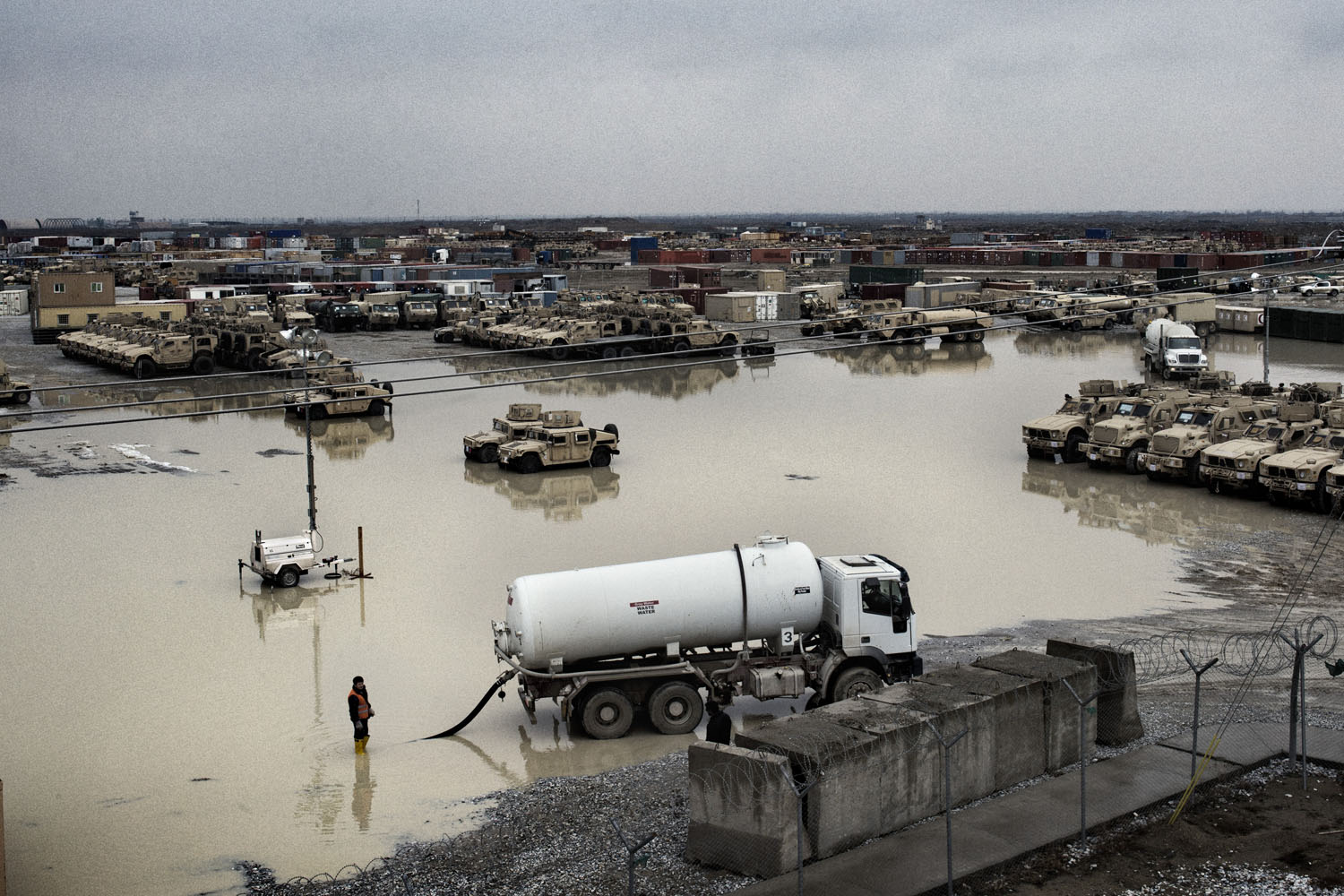 Civilian contractors work to drain a large puddle following a January rain at Bagram. The yard holds armored combat vehicles that have been inspected and processed in preparation for shipment to the United States.