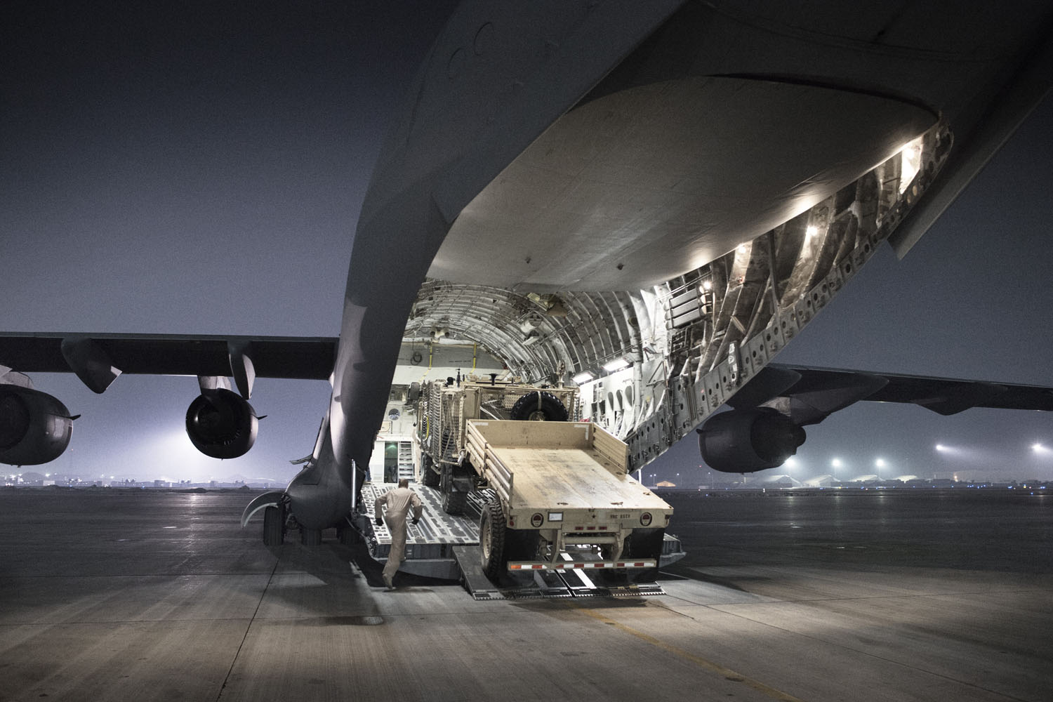 An airman climbs aboard a C-17 cargo aircraft at Bagram Airbase while loading an armored vehicle and trailer for a flight out of the country. When snow closes some key routes out of the country, the U.S. military ships nearly 70 percent of the equipment leaving the country by air, both through civilian contractors and Air Force cargo flights.