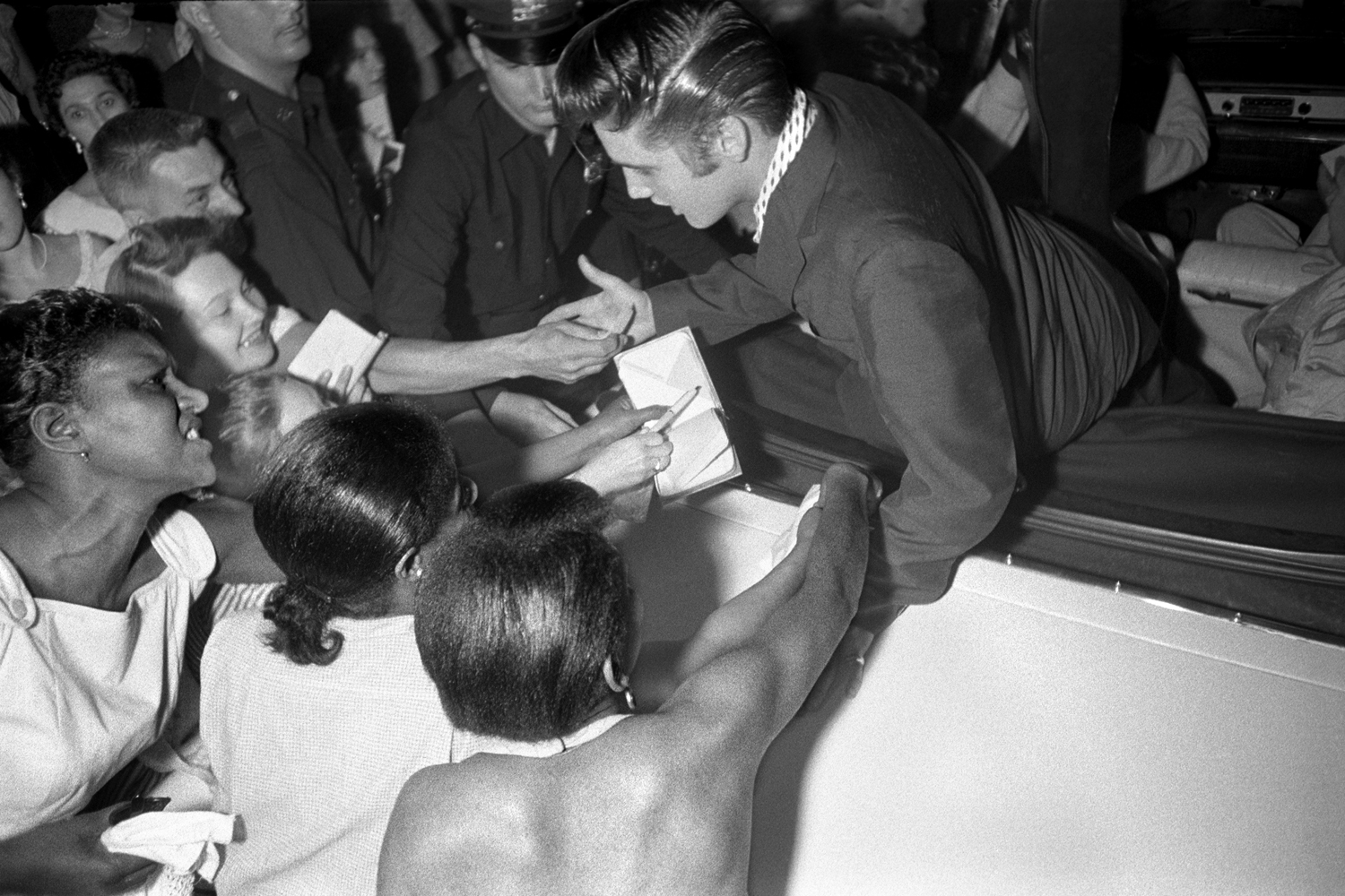 July 1, 1956. The Hudson Theatre, New York. Elvis leaving the theatre where he had performed on the Steve Allen show. This one is unusual...the black girls who are fans are trying to touch him. You think of Little Richard, but you don't think of Elvis and black fans.