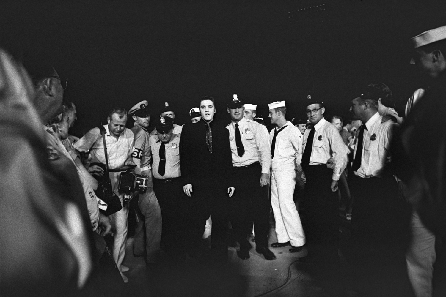 July 4, 1956. Russwood Park, Memphis. Elvis is entering the stadium escorted by the local police and fire department, but also by the Shore Police of the Navy. This was Elvis' first charitable benefit show, with proceeds going to The Cynthia Milk Fund and the Variety Club's Home for Convalescent Children.
