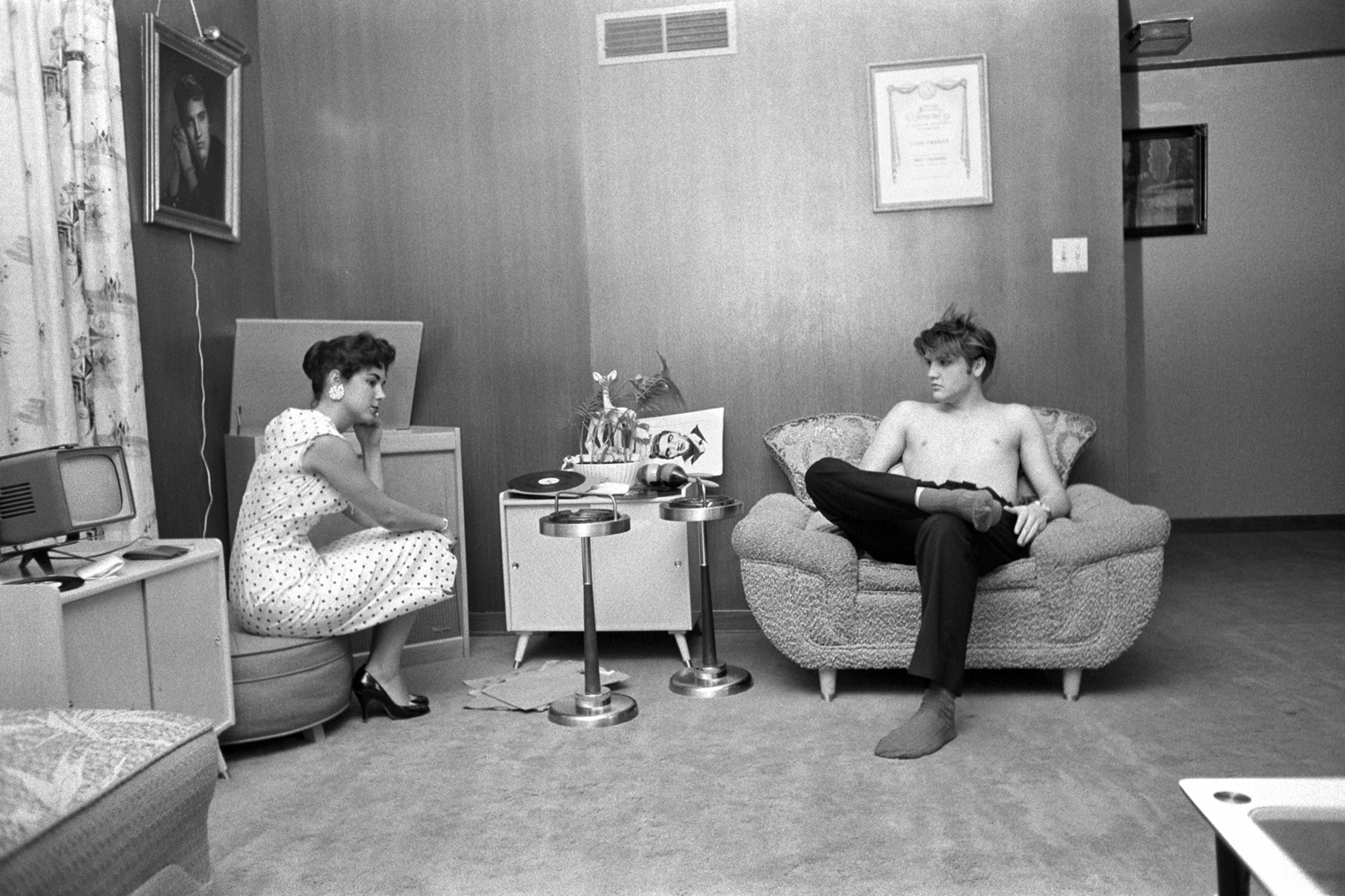 July 4, 1956. 1034 Auburn Drive, Memphis. With Barbara Hearn listening to playback. The shot of Elvis on the wall is his first publicity shot (the gold frame with a light over the top.) And his mother liked it so much that she went back to the photographer and had it hand painted in color on canvas…looked like a museum painting!                                                              Here, Elvis is testing the three songs that he recorded a few days earlier. He had gotten a quick acetate cut, which would play for about 50 takes before it disintegrated. He tried to dance with her, but he was all sweated up, and she said  after you're showered up.  He wanted to know if the music was danceable — she said no.