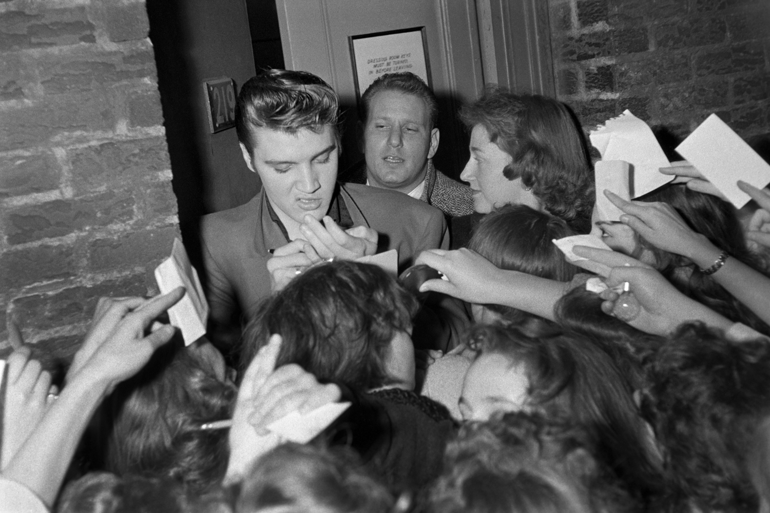 March 17, 1956. Studio 50 New York. This was the crowd after the Dorsey Brothers 'Stage Show.'  I just like the snarl. There were about a hundred well wishers at the backstage entrance and fans asking for autographs. The girl on the right was helping with slips of paper — she was so happy to be close to him. And this guy was concerned with keeping Elvis warm.