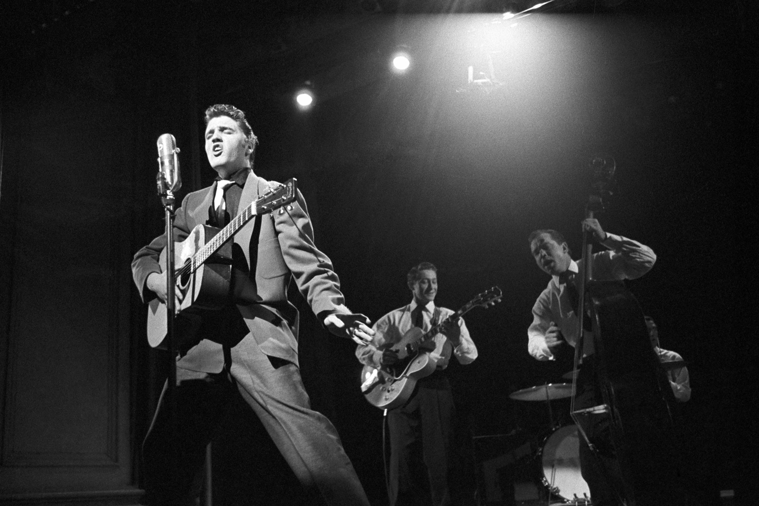 March 17, 1956. Studio 50 in New York. This image became a Swedish postage stamp, representing the 50th anniversary of Rock and Roll. This is the performance on the Dorsey Brothers 'Stage Show.' In the background is Bill Black on bass, Scottie Moore on guitar and, hidden behind the bass, DJ Fontana on drums.