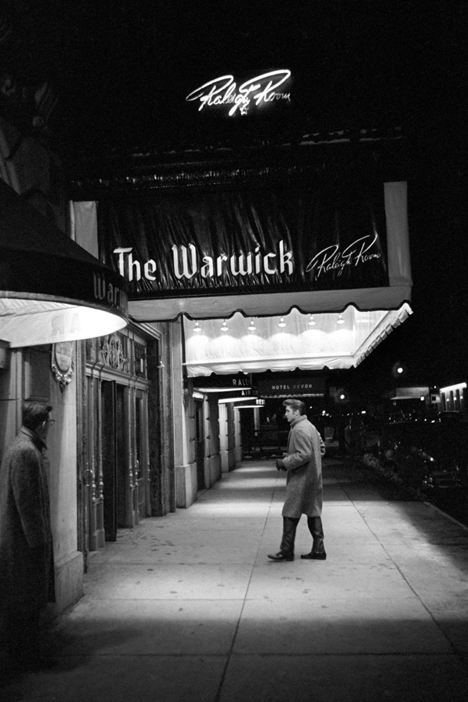 Each of the following captions include Wertheimer's first-person memories.                                                              March 17, 1956. The Warwick, New York. A cold winter's day in March. Here Elvis is walking into his hotel alone. He and I were back there, in between the rehearsal and the evening performance [on the Dorsey Brothers  Stage Show ]. The little black spots on the sidewalk? That's chewing gum that's been ground into the pavement.