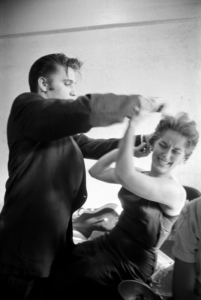 June 30, 1956. Backstage at the Mosque Theatre, Richmond, Virginia. Elvis didn't like his women with corsets or hairspray — he was more into the natural look. Here he is messing up Bobbi Owen's hair, trying to annoy her in a cute way but she took it so seriously. I wanted  something to show his character and to show he could be playful and that he liked messing around. With Elvis, you never knew what or where he was coming from. He was so spontaneous, you had to be ready, otherwise you'd miss it. That was the fun of it.